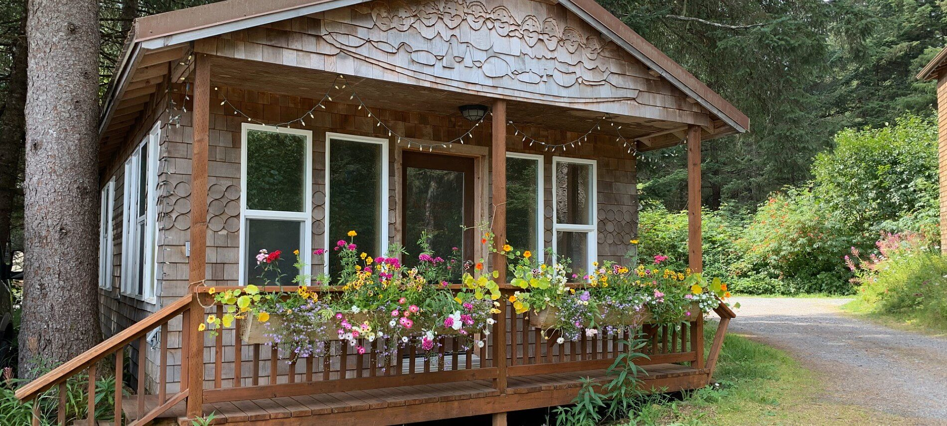 Cute brown cabin with decorative shingles, flowers on the front porch and woods all around