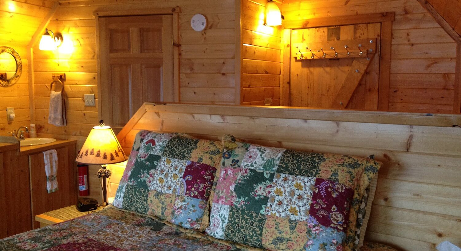 Queen bed in a flowered quilt with a wood headboard in a cozy cabin