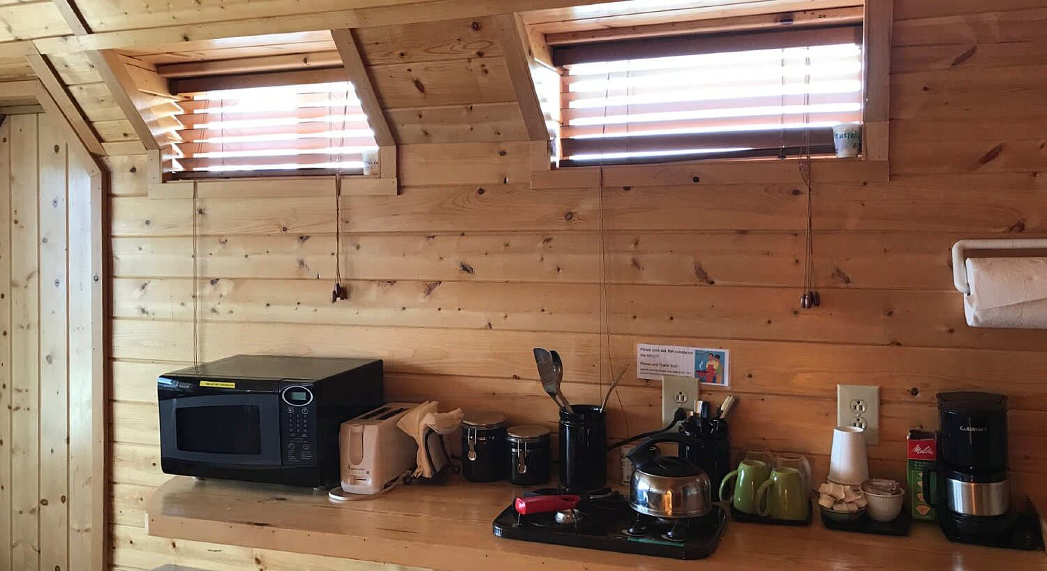 Kitchenette counter in a cabin with microwave, toaster, coffee pot and other kitchen essentials