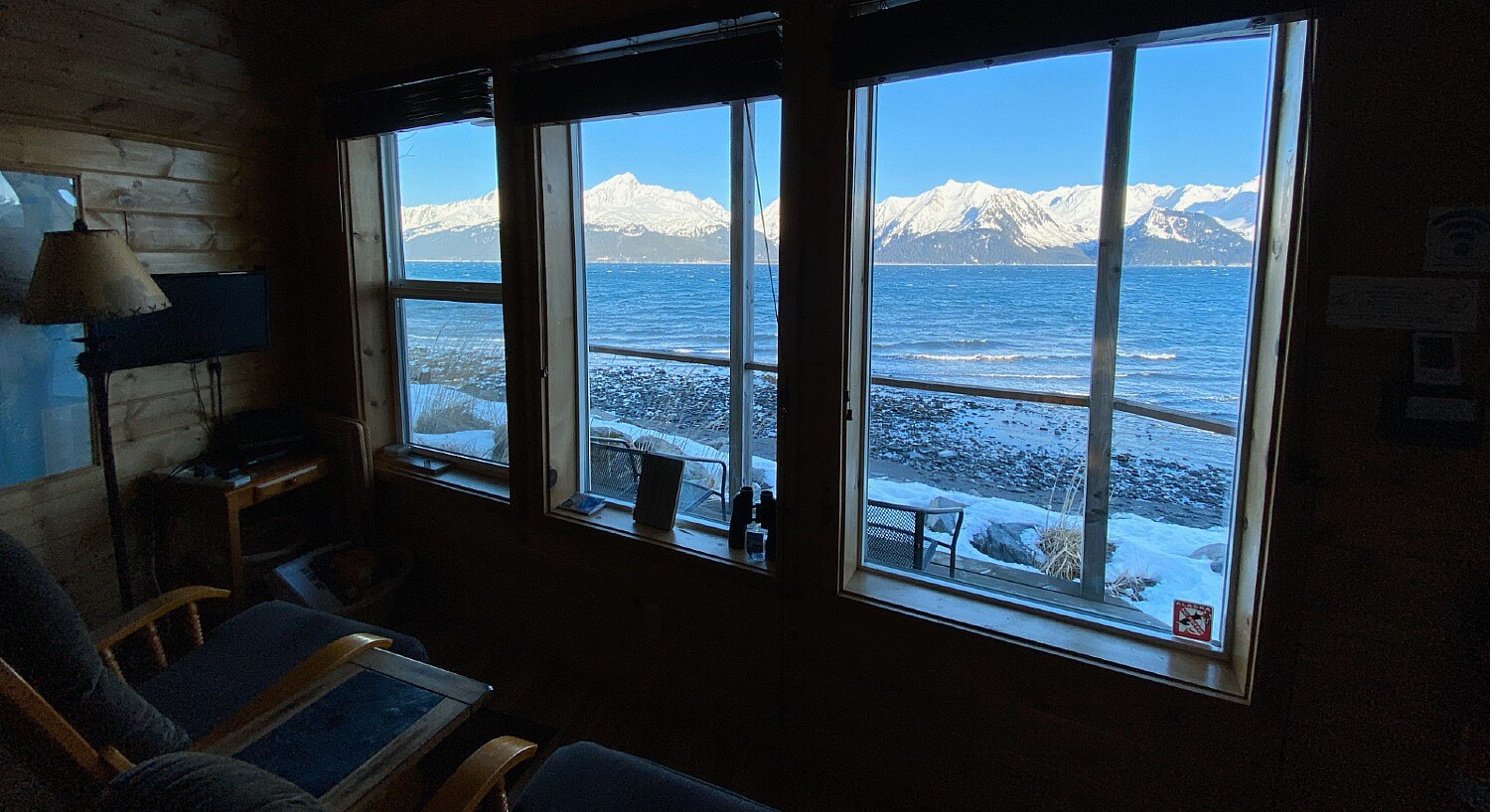 Two glider rockers sitting in front of three large windows overlooking a bay and snow-capped mountains in winter