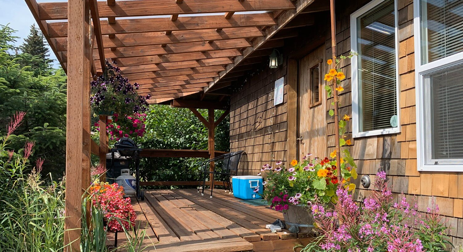 Spacious front porch of a wood cabin with pergola, chairs, bbq, and many colorful flowers