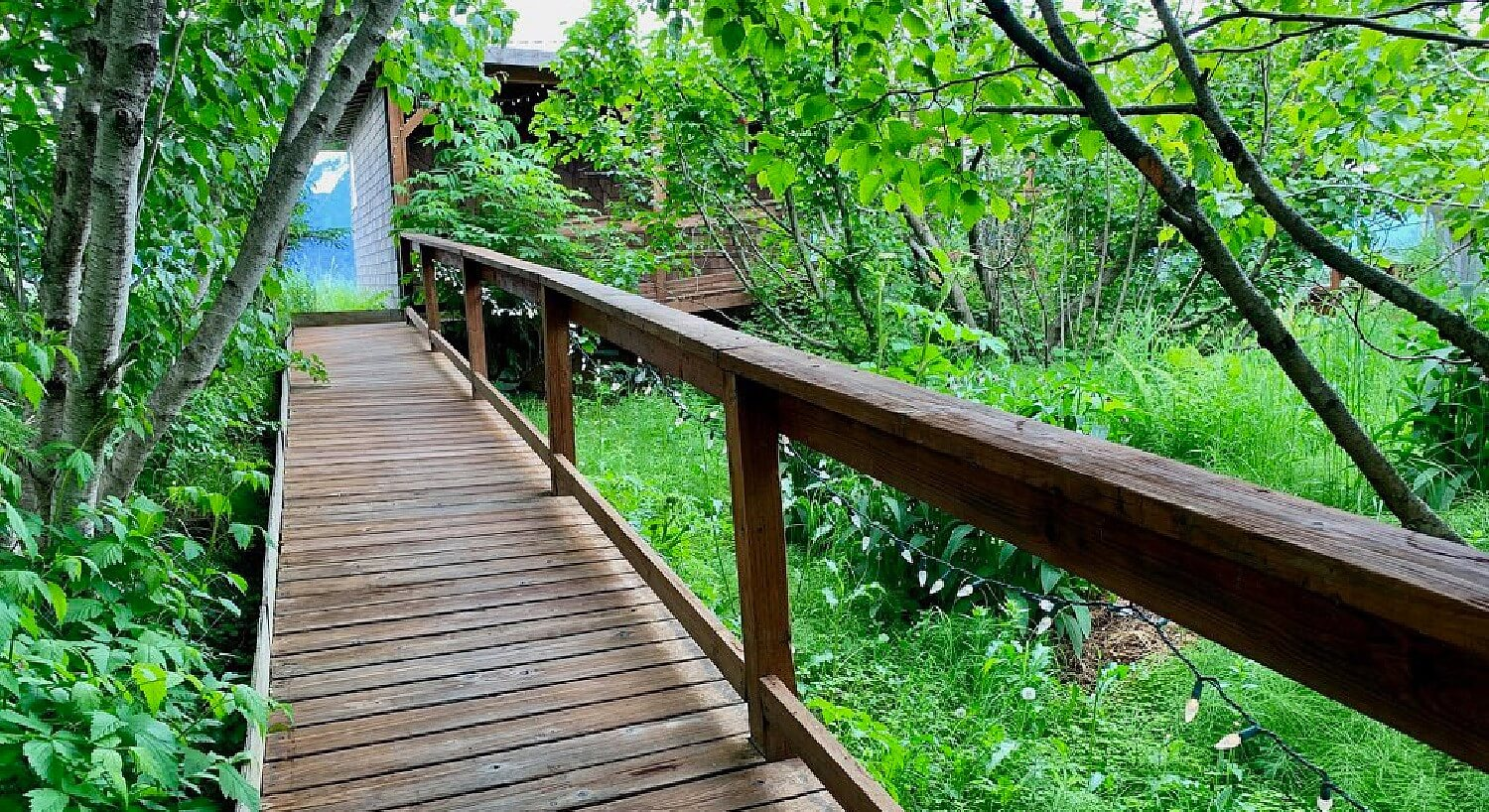 Wooden walkway with railing surrounded by trees leading up to a cabin