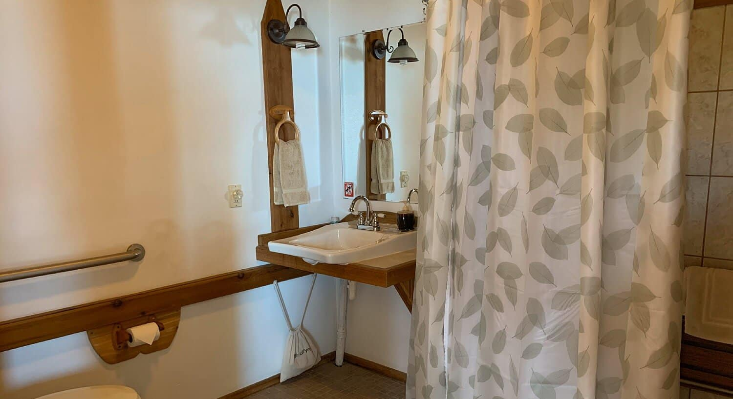 Bathroom featuring wood vanity and white sink and shower with grey and white shower curtain