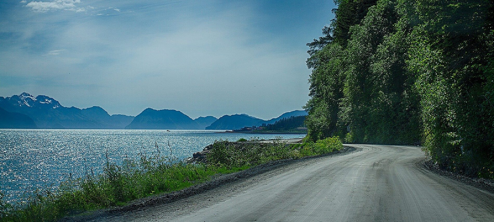Empty winding road next to wooded area following the edge of a large lake surrounded by a mountain range