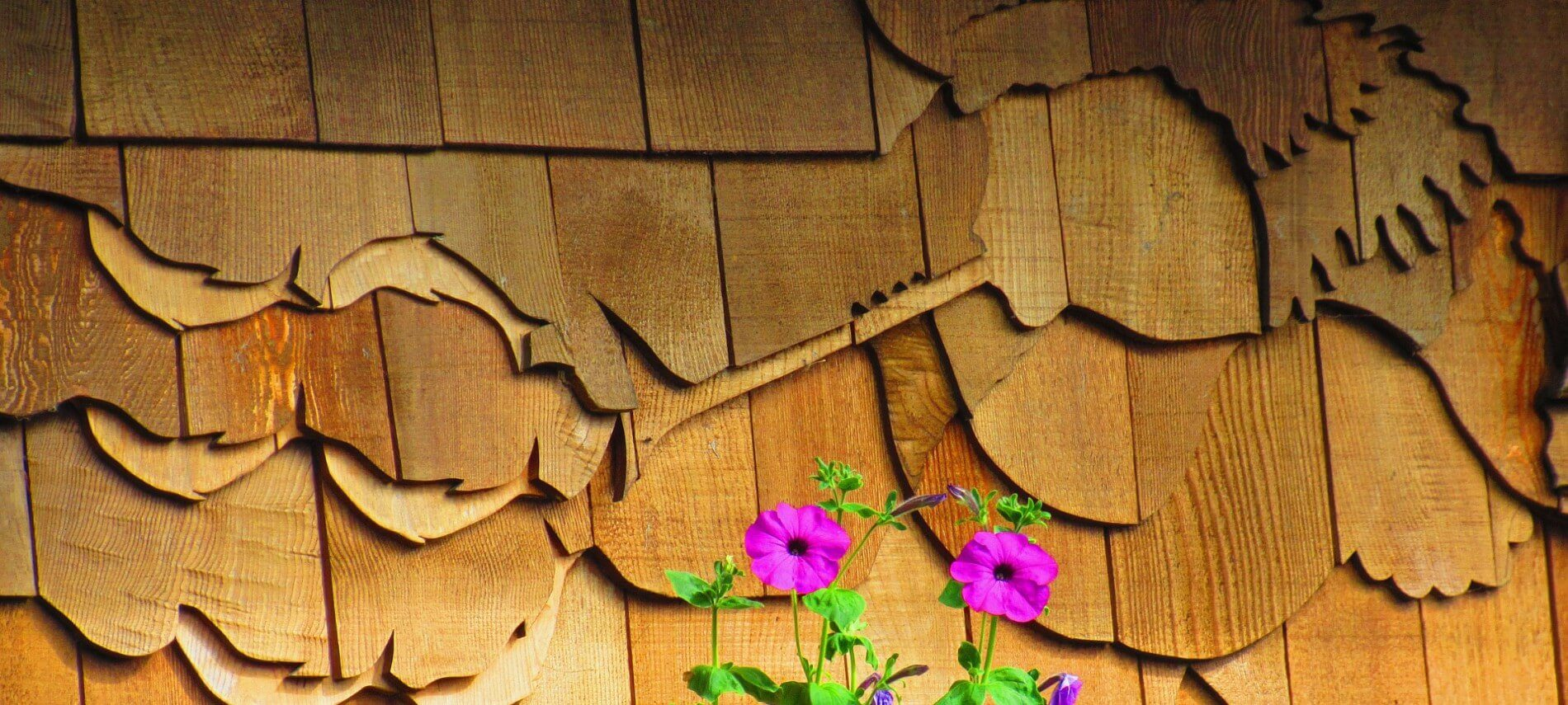 Side of a cabin with brown shingles cut into the shape of a woman blowing a horn with purple flowers