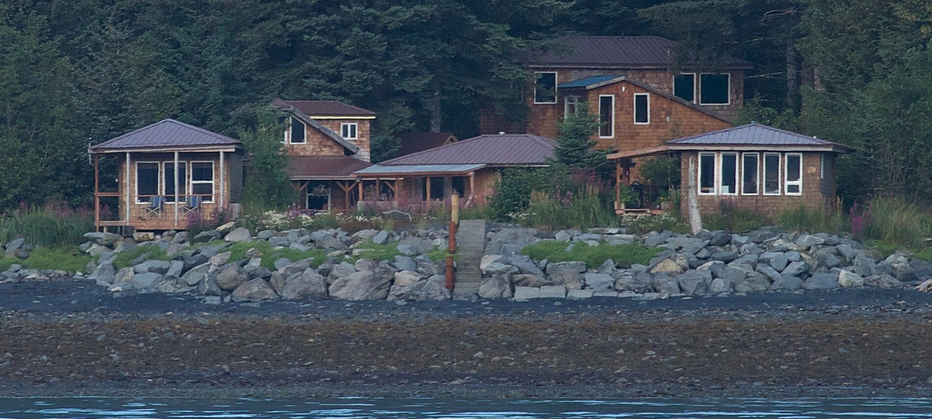 View of a rocky shore with five small brown cabins nestled among tall evergreen trees