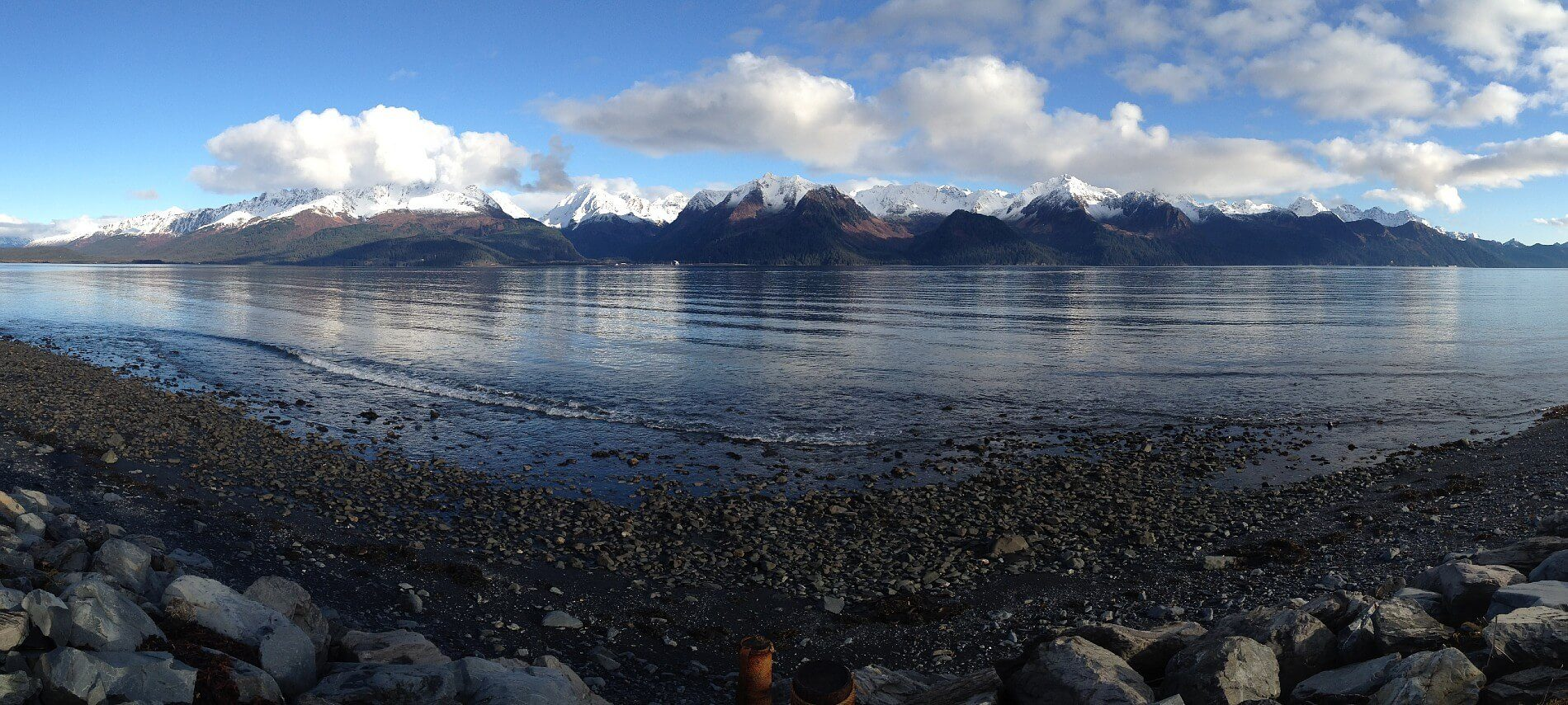 The edge of a rocky beach by a large calm bay surrounded by snow-capped mountains and clouds in a blue sky