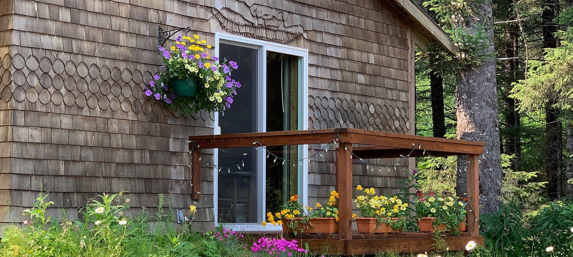 Brown cabin with decorative shingles and side porch with colorful flowers and hanging white lights