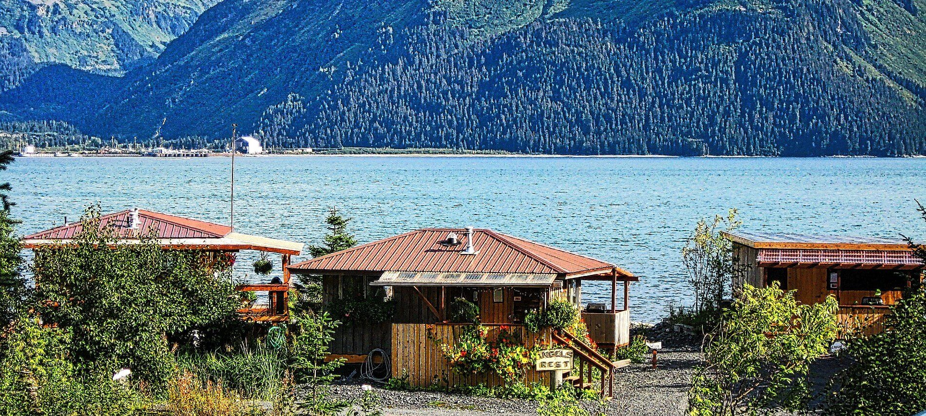 Three small brown cabins next to a large bay with tree covered mountains in the background