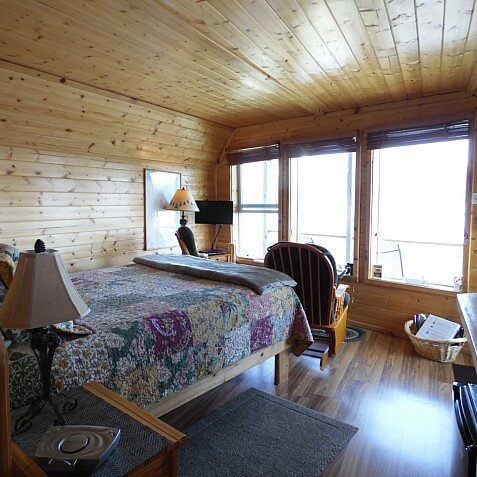 Spacious wood cabin guest room with bed, dresser, chair, and three large windows