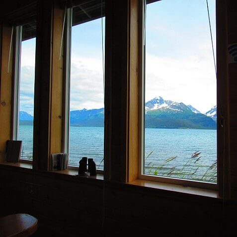 Guest room with three large windows looking out into a picturesque view of water and snow-capped mountains