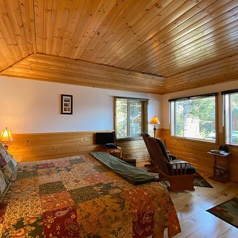 Large guest room with wood paneled ceiling, king bed and large windows overlooking wooded area