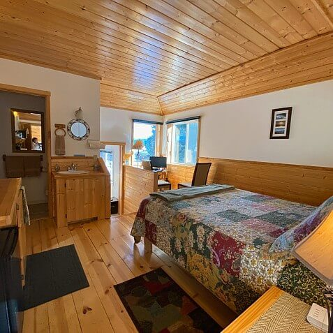 Gorgeous wood cabin guest room with wood floors, wood ceiling and bed, dresser, sitting chair and guest bathroom