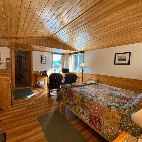 Spacious guest room with wood floors, wood paneled ceiling and bed, dresser and two sitting chairs