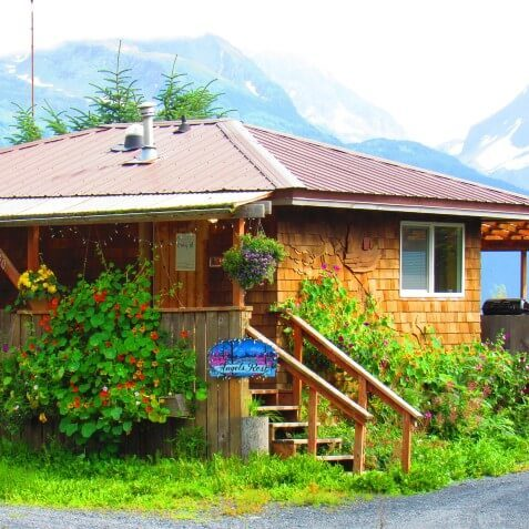 Cute brown cabin with lush green landscaping, front steps and tall snow-capped mountains behind