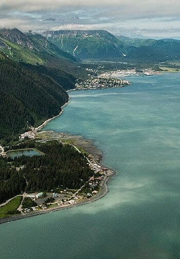 Gorgeous overhead view of large body of water next to tree covered mountains and homes around the edge of the land