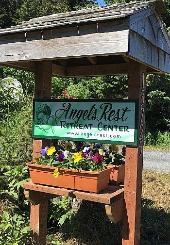 Tall wooden stand with green business sign and planter box with pink, yellow and purple flowers