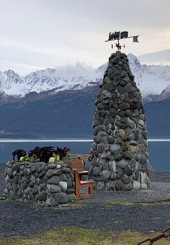 Tall rock sculpture with brown sitting benches by a large lake and snow-capped mountains