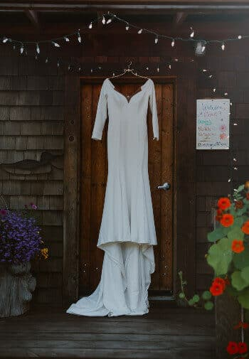 bridal gown hanging on wood door with red flowers next to walk