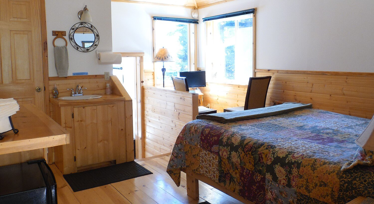 Cabin guest room with wood floors, queen bed, small vanity with sink and two chairs in a nook with tv and windows