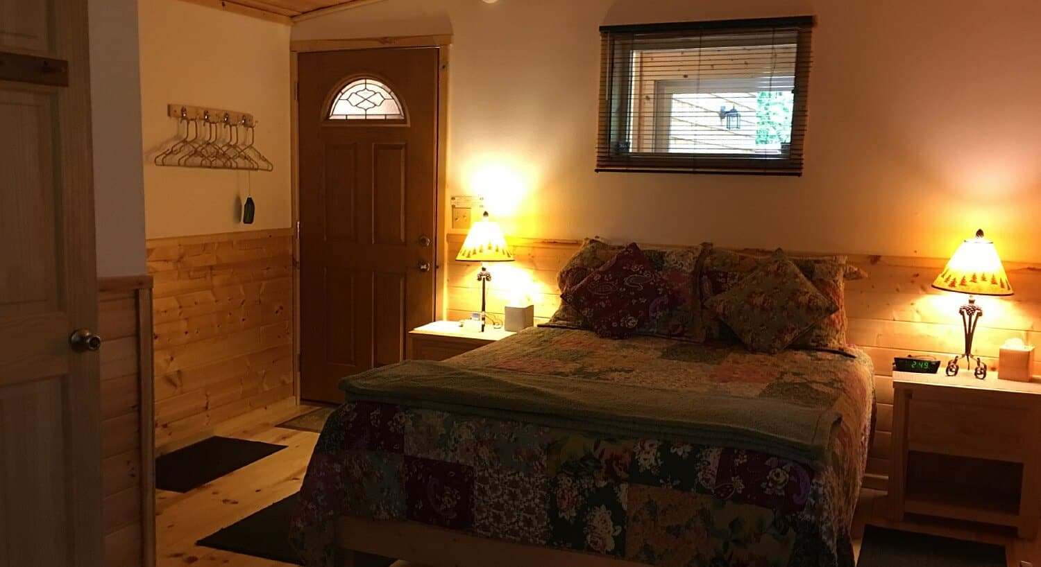 Cabin guestroom with queen bed, colorful quilt, bed stands with lamps and wood floors