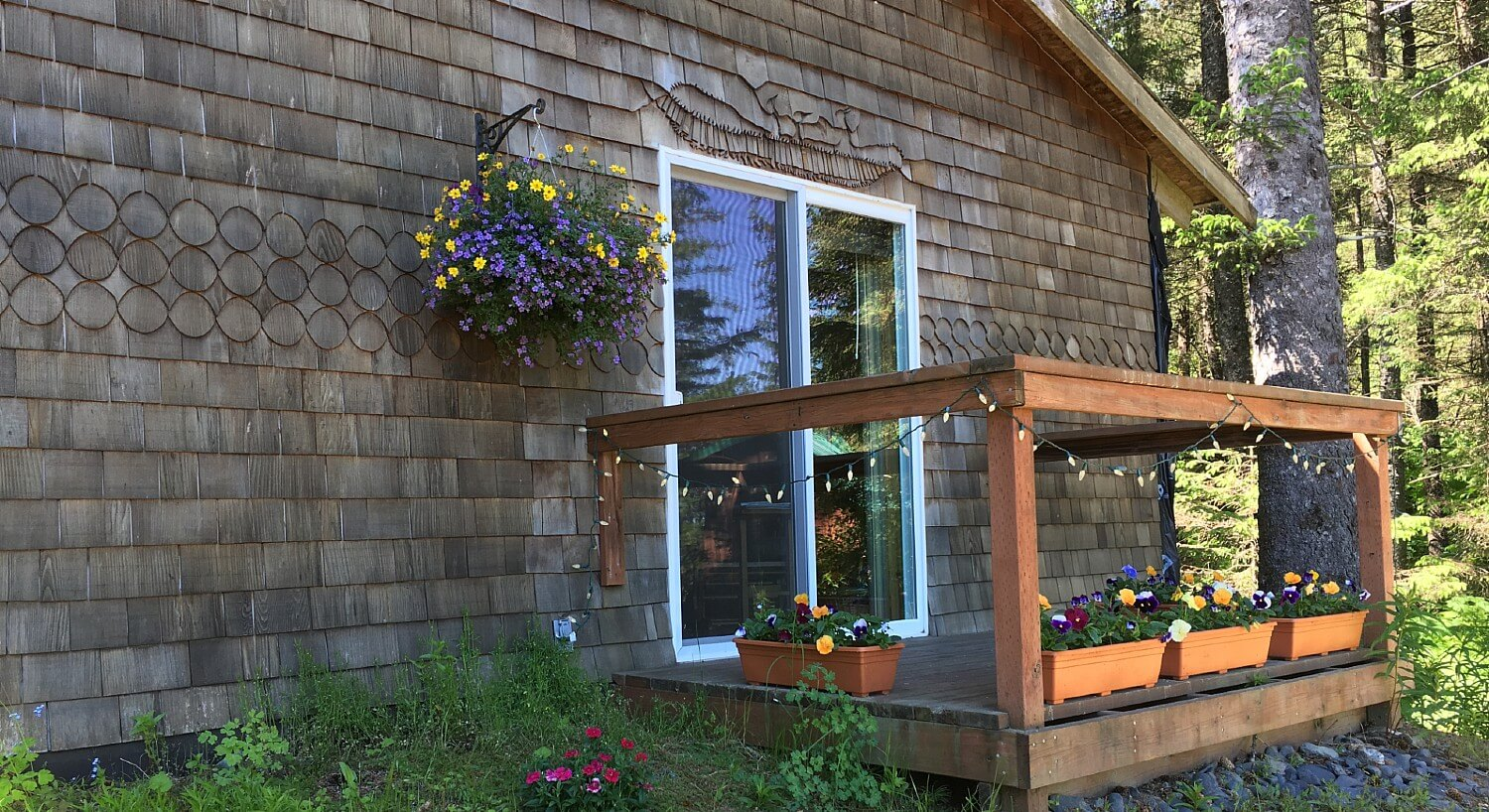 Small side porch of a brown wood cabin with hanging lights and several flower baskets