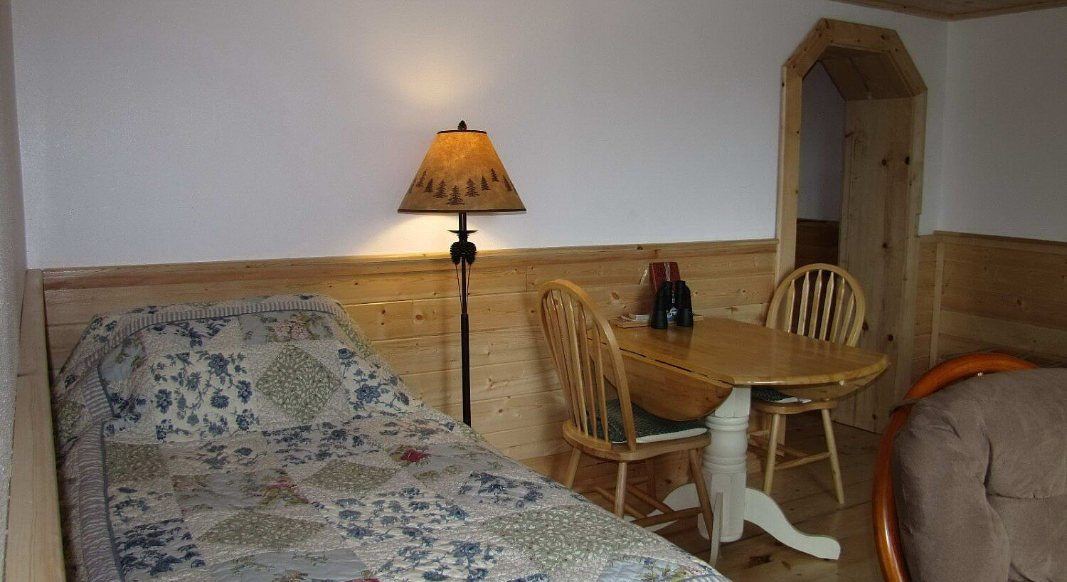 Cozy cabin guest room with twin bed, tall lamp, drop-leaf table with two chairs and plush glider rocker