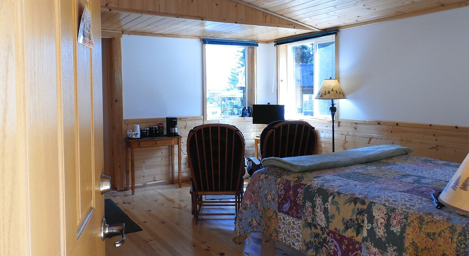 Cabin guest room featuring wood paneled walls and ceiling, queen bed, and two sitting chairs in front of large windows