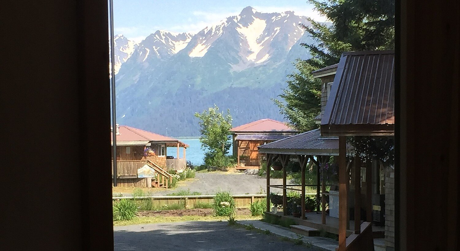 View out of a large window showing several small brown cabins in front of a bay and tall snow-capped mountains