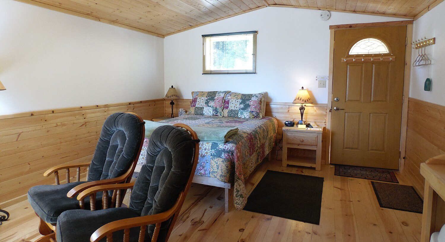 Cozy cabin bedroom featuring queen bed with colorful quilt, bed stands with lamps and two grey plush sitting chairs
