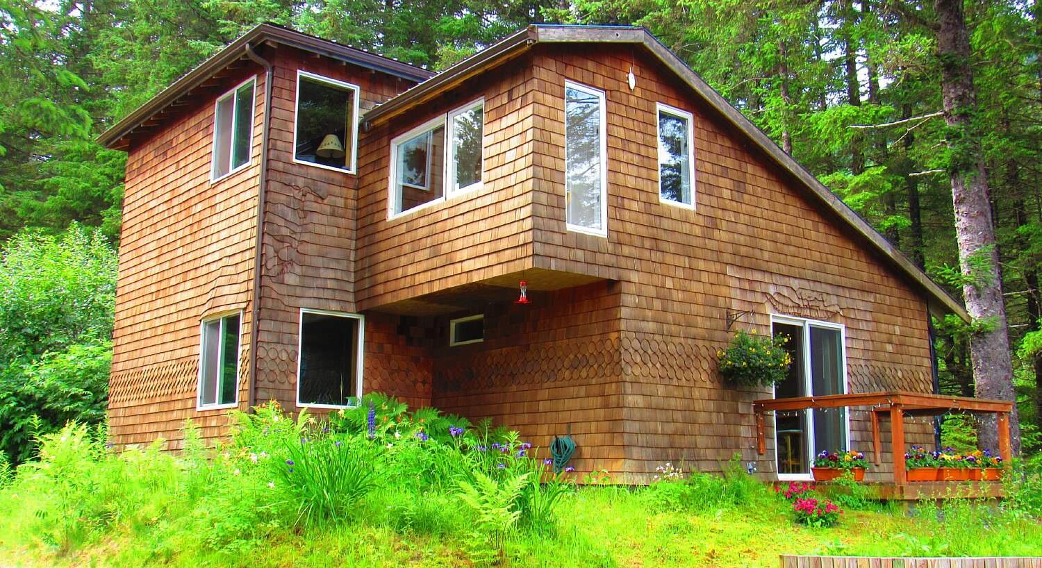 Tall brown shingled cabin with lots of windows nestled in a wooded area with green trees