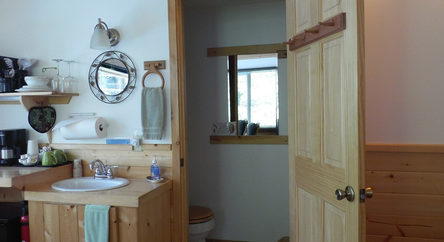 Cabin bathroom with single sink, room with toilet and coffee bar area with dishes and coffeemaker.