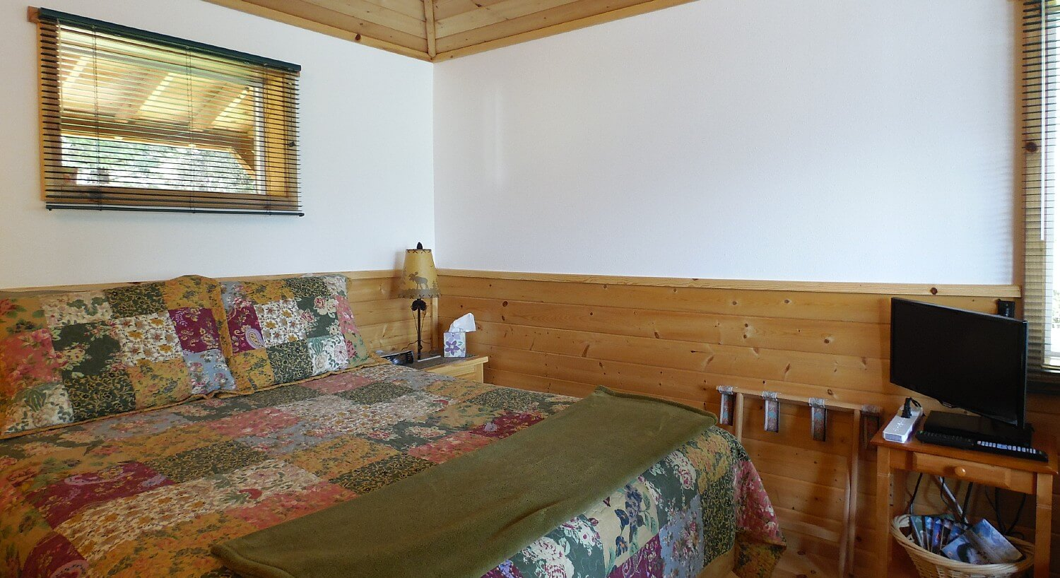 Cabin room with queen bed covered in a colorful quilt, small tv table, lamp and two windows