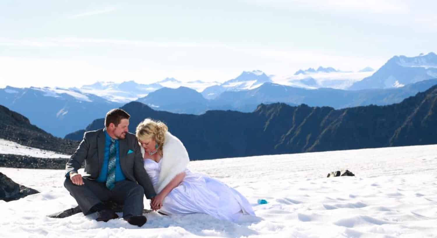 bride in wedding gown and groom in gray suite sitting in snow with snow-capped mountains in distance