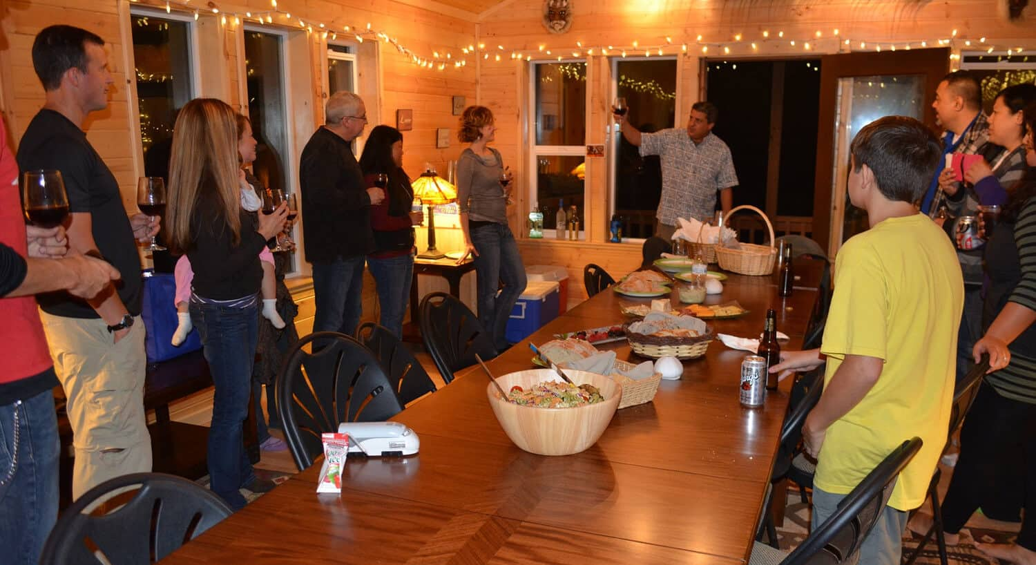 guests holding beverages for toast wearing casual clothing in room with long table with food for celebration