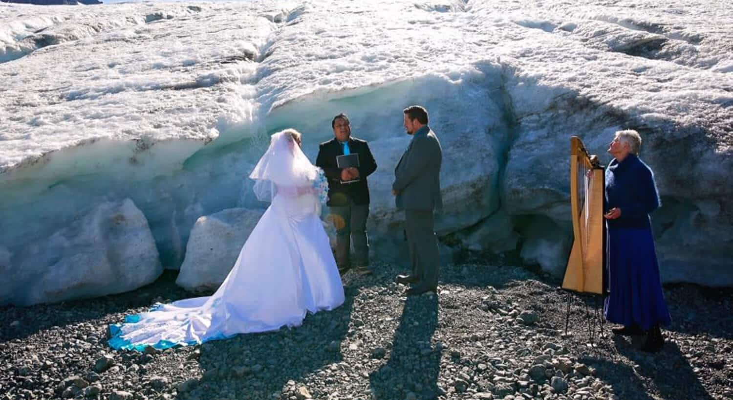 bride with long train laying on ground and groom standing in front of preacher by glacier with woman standing by harp