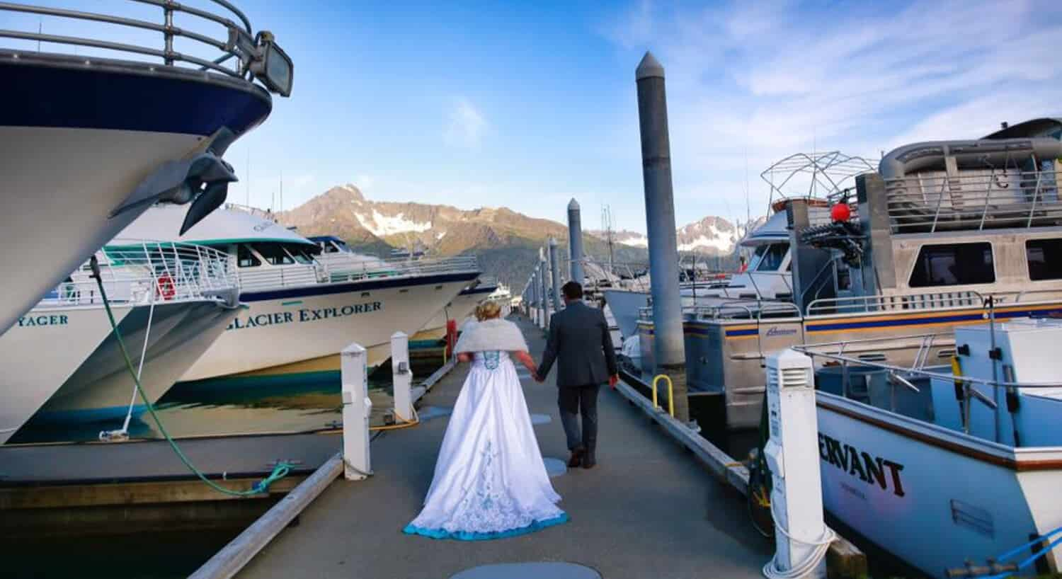 bride wearing shawl over gown and groom holding hands walking along pier with large boats anchored on both sides