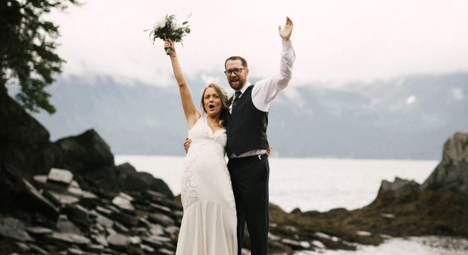 bride holding bouquet over head and groom waving hand standing on rocks giving holler with snow-capped mountains in background