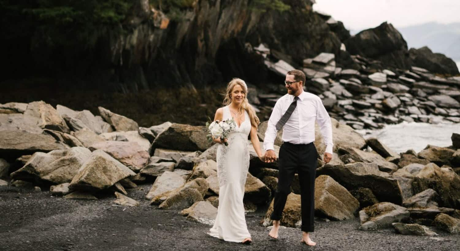 bride and groom with bare feet holding hands walking away from rocks by water