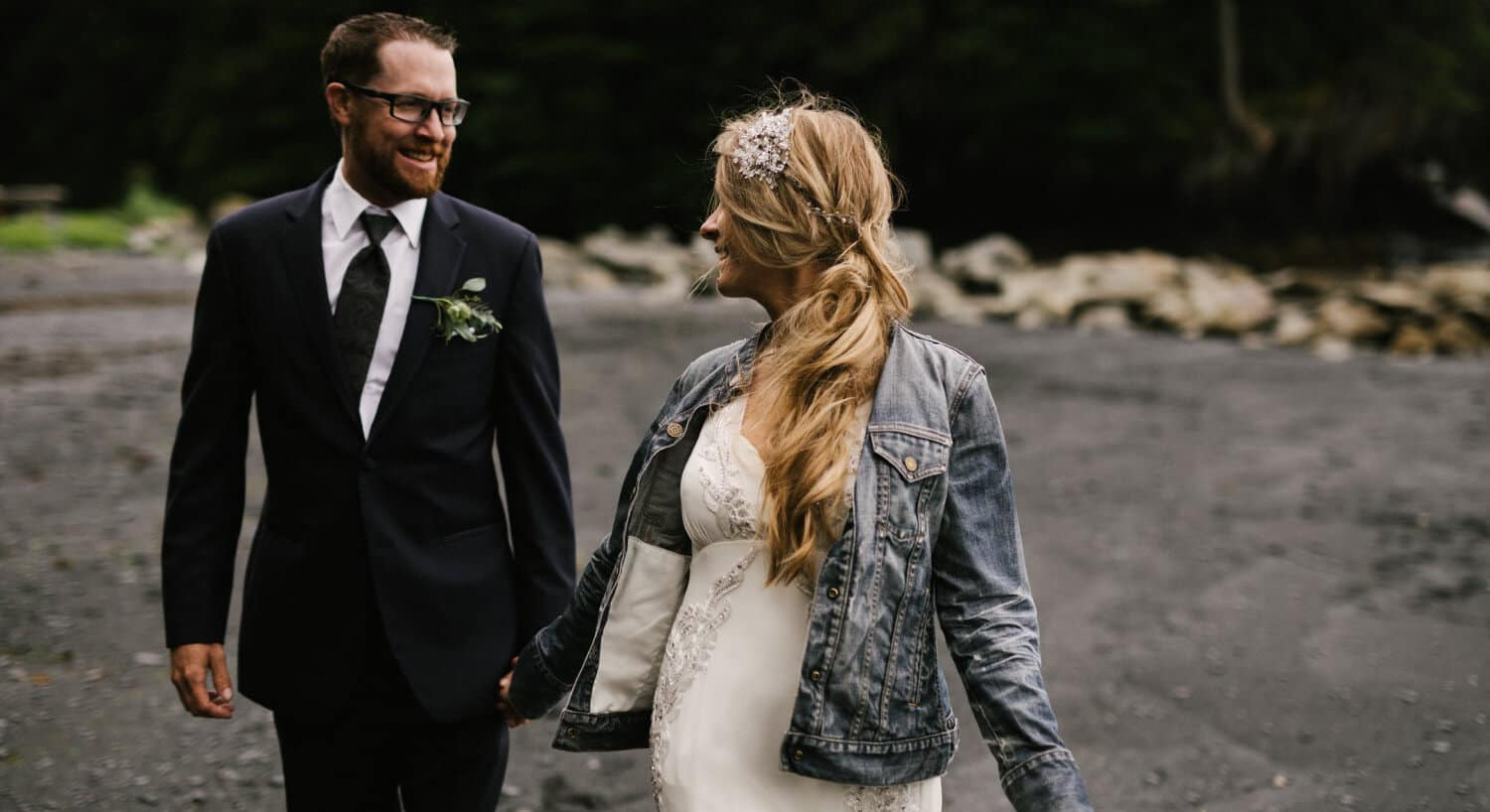 bride in gown wearing blue jean jacket looking over shoulder toward groom wearing blue suit and tie with big smile
