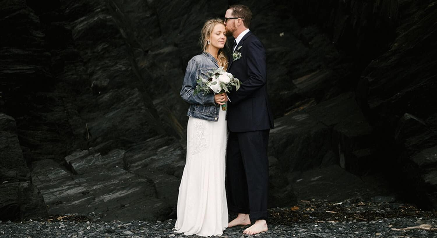 bride and groom standing with bare feet on rocks with black rocks behind bride holding bouquet with groom kissing bride's forehead