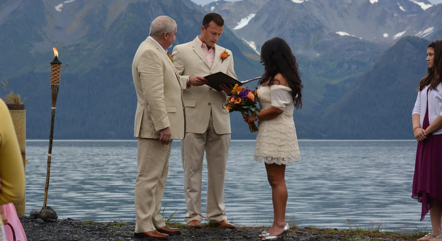 preacher performing wedding ceremony with bride and groom in cream clothing standing along edge of water with lit tiki torch mountain in background