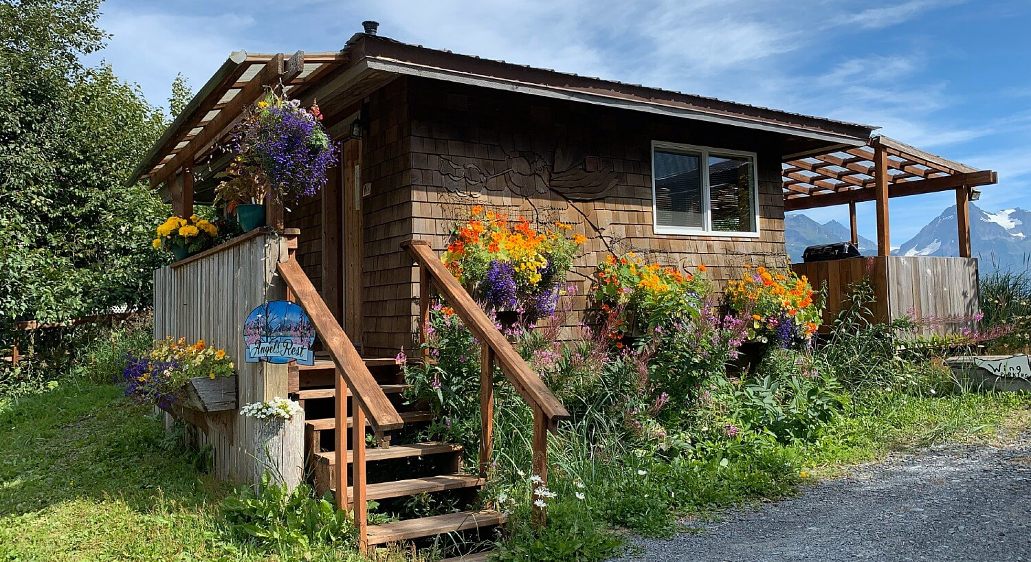 Brown cabin with flat roof, small porch and staircase and colorful flowers with mountains in background