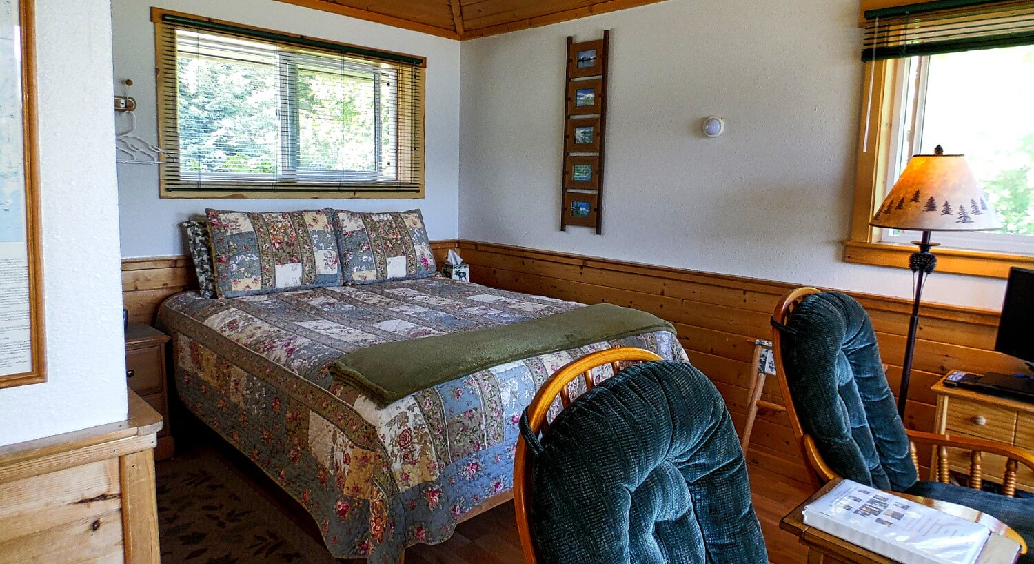 Room in a cabin featuring queen bed with blue quilt, wood paneling, and two plush sitting chairs