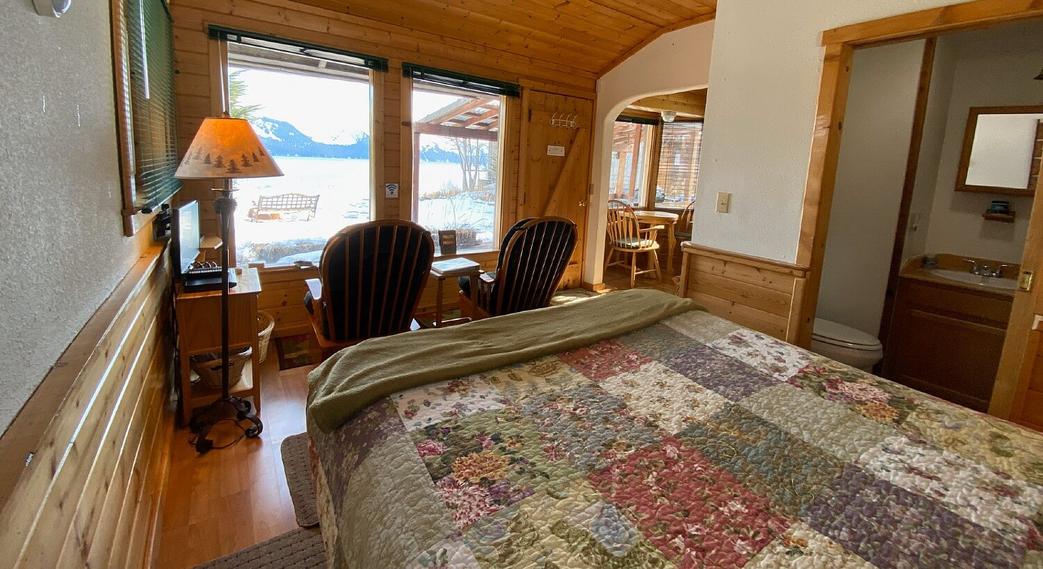 Room in a cabin featuring queen bed with a quilt and two sitting chairs in front of two large windows overlooking water and mountains