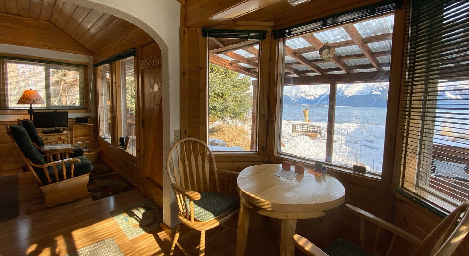 Corner of a cabin featuring sitting chairs and a table with two chairs under large windows looking out over water and mountains