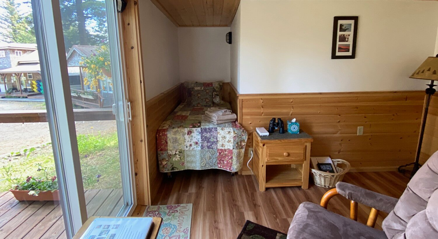 Open room with medium wood rustic paneling to chair rail with cream walls, hardwood floor, large sliding glass door and bed with quilt tucked away and nook of room